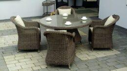 Okrągły stół ogrodowy w zestawie z czterema fotelami z poduszkami na siedzisko i oparcie.